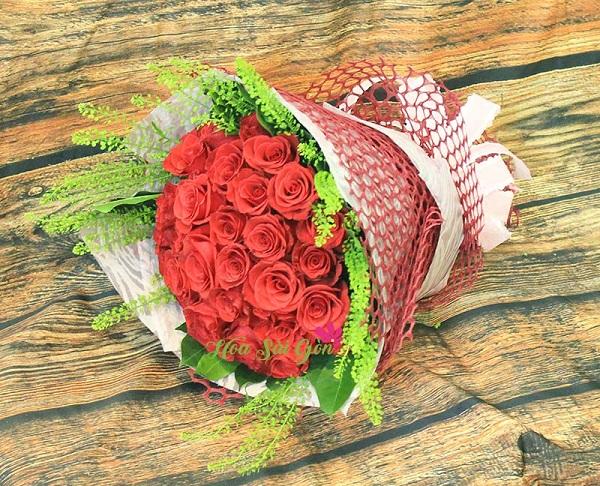 Bó hoa là sự kết hợp của vẻ đẹp quyến rũ của những bông hồng đỏ nổi bật trên nền lá xanh